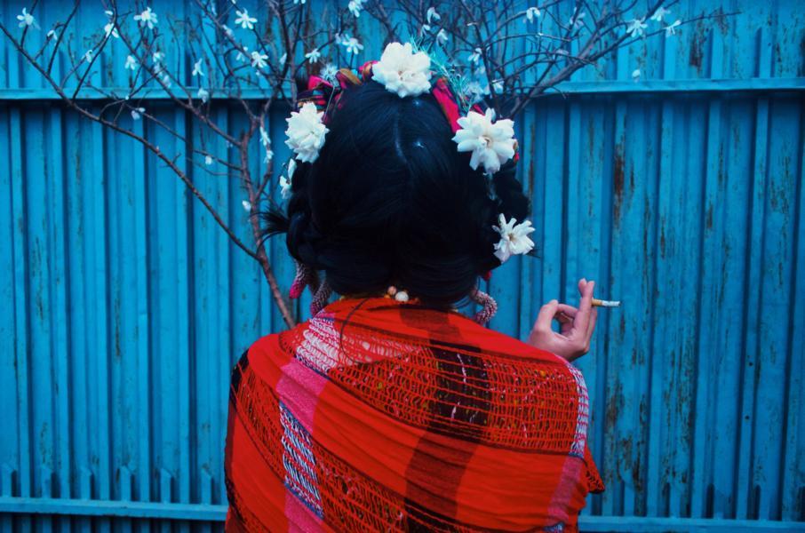 Eine Dame mit einer Zigarette in der Hand und weißen Blumen im Kopf