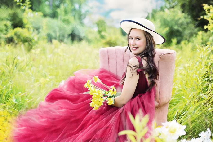Eine Lachende Dame in der Natur mit einem Kleid und gelben Blumen in der Hand