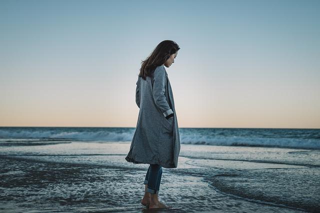 Eine Dame die am Meer spaziert