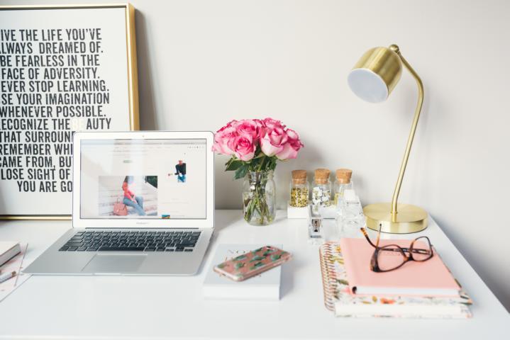 Ein Laptop auf dem Schreibtisch. Pinke Rosen, Eine Tischlampe und Notizbücher