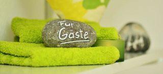 Gästehandtuch in Grün mit einem Dekor Stein