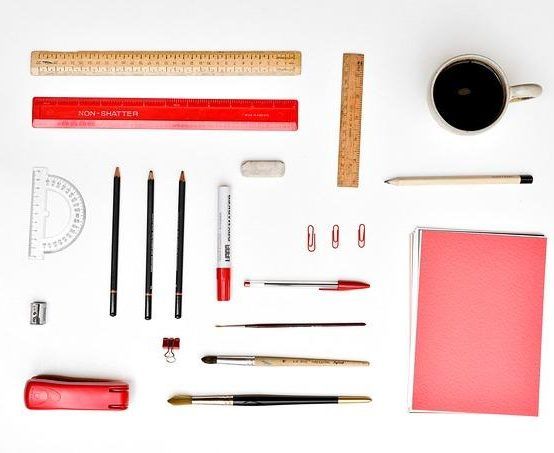 Ein ordentlicher Tisch mit vielen Gegenständen wie Papier, Stifte, Kaffee und Lineal