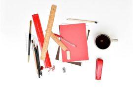 Ein unordentlicher Tisch mit vielen Gegenständen wie Papier, Stifte, Kaffee und Lineal