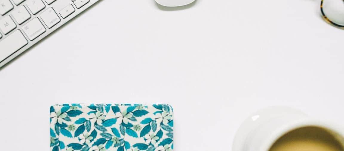Ein ordentlicher Schreibtisch mit einer Brille, Kaffee und Notizbuch drauf