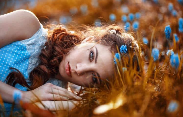 Die Frau im hellblauen Kleid und blauen Blumen