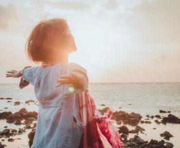 Frau am Wasser mit ausgestreckten Händen