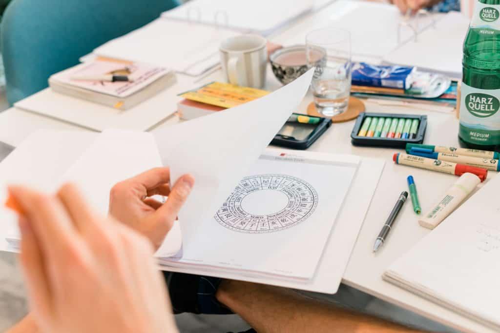 Ein Mann sitzt vor einem Feng-Shui Ordner und schaut sich eine Grafik an