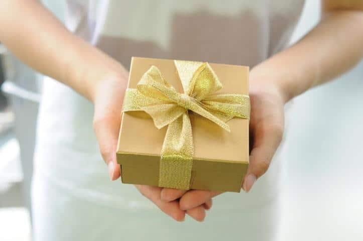 """Ein Geschenkbox in Gold in der Hand von einer Dame mit dem Text """" Das perfekte Geschenk"""""""