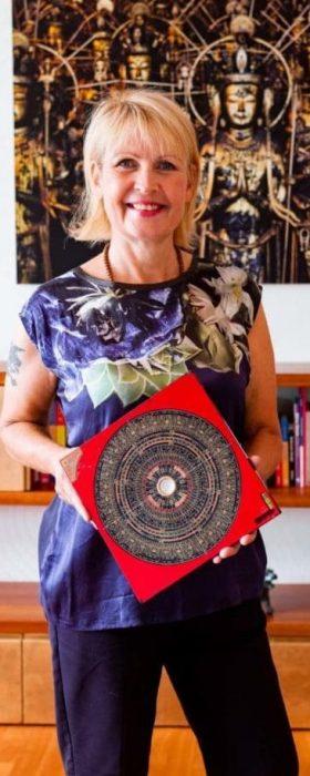 Feng Shui Beraterin Petra Coll Exposito mit Kompass in der Hand im Wohnzimmer