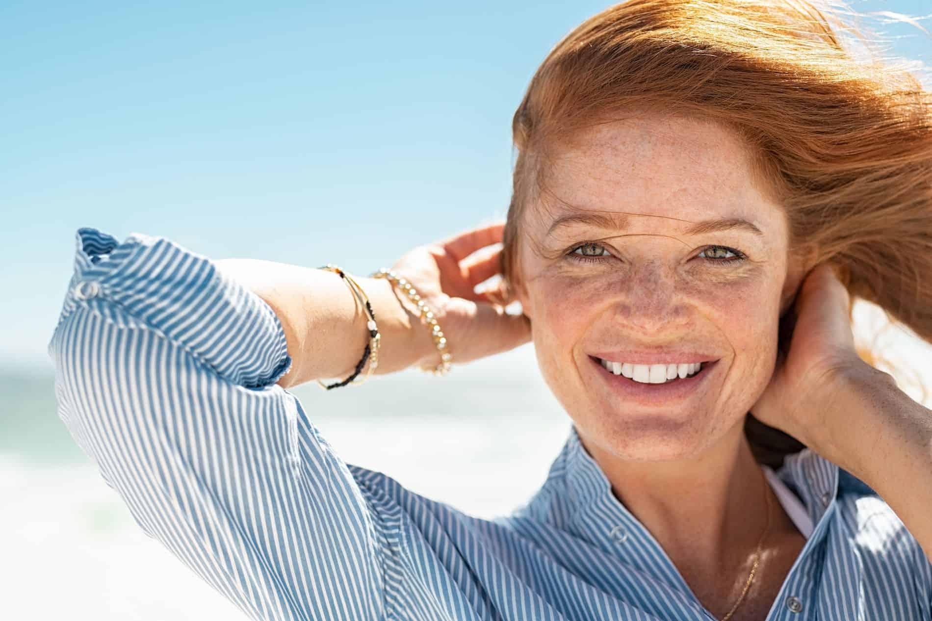 Eine Frau mit Sommersprossen lächelt in die Kamera